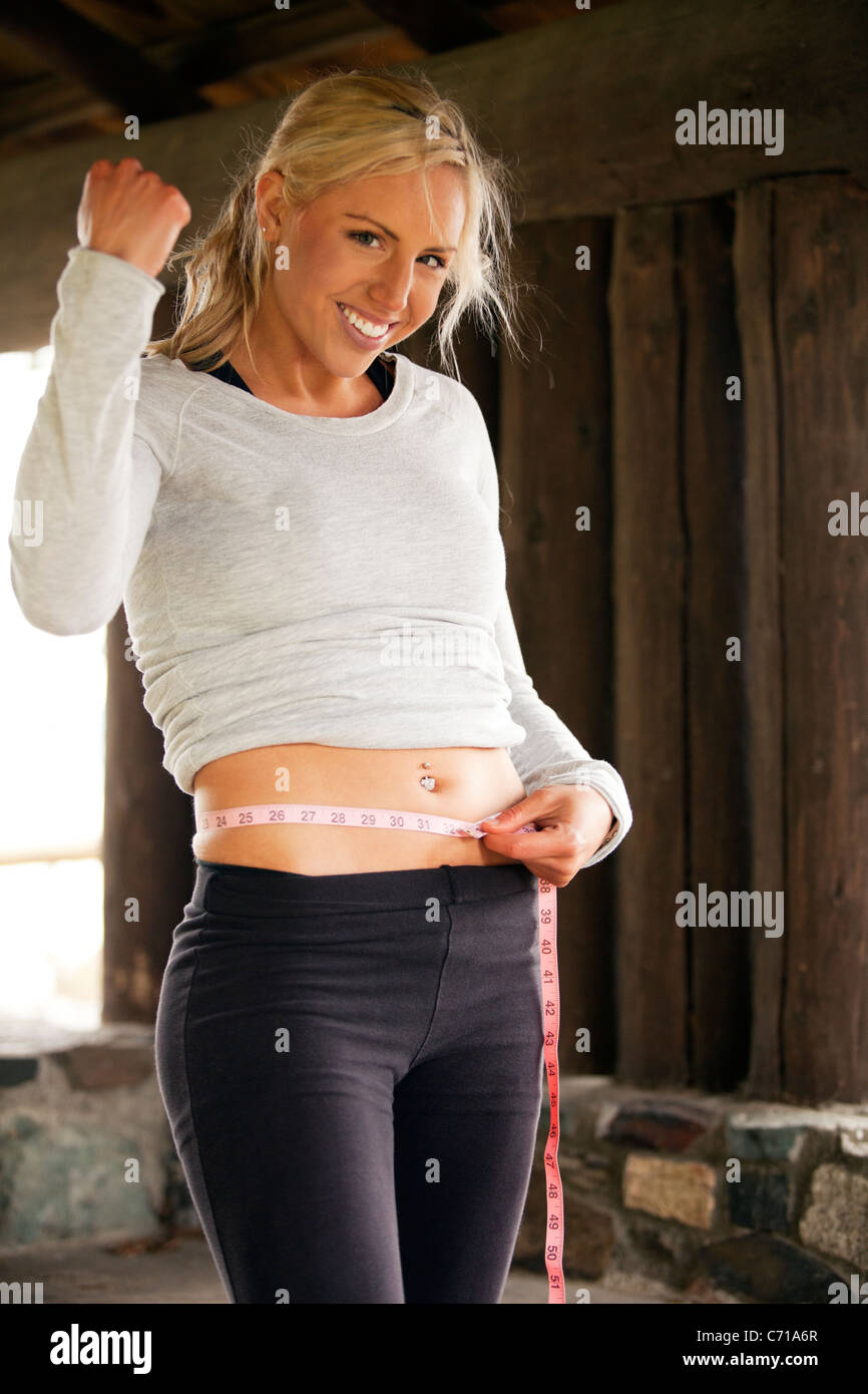 A healthy woman celebrates as she measures her waist. - Stock Image