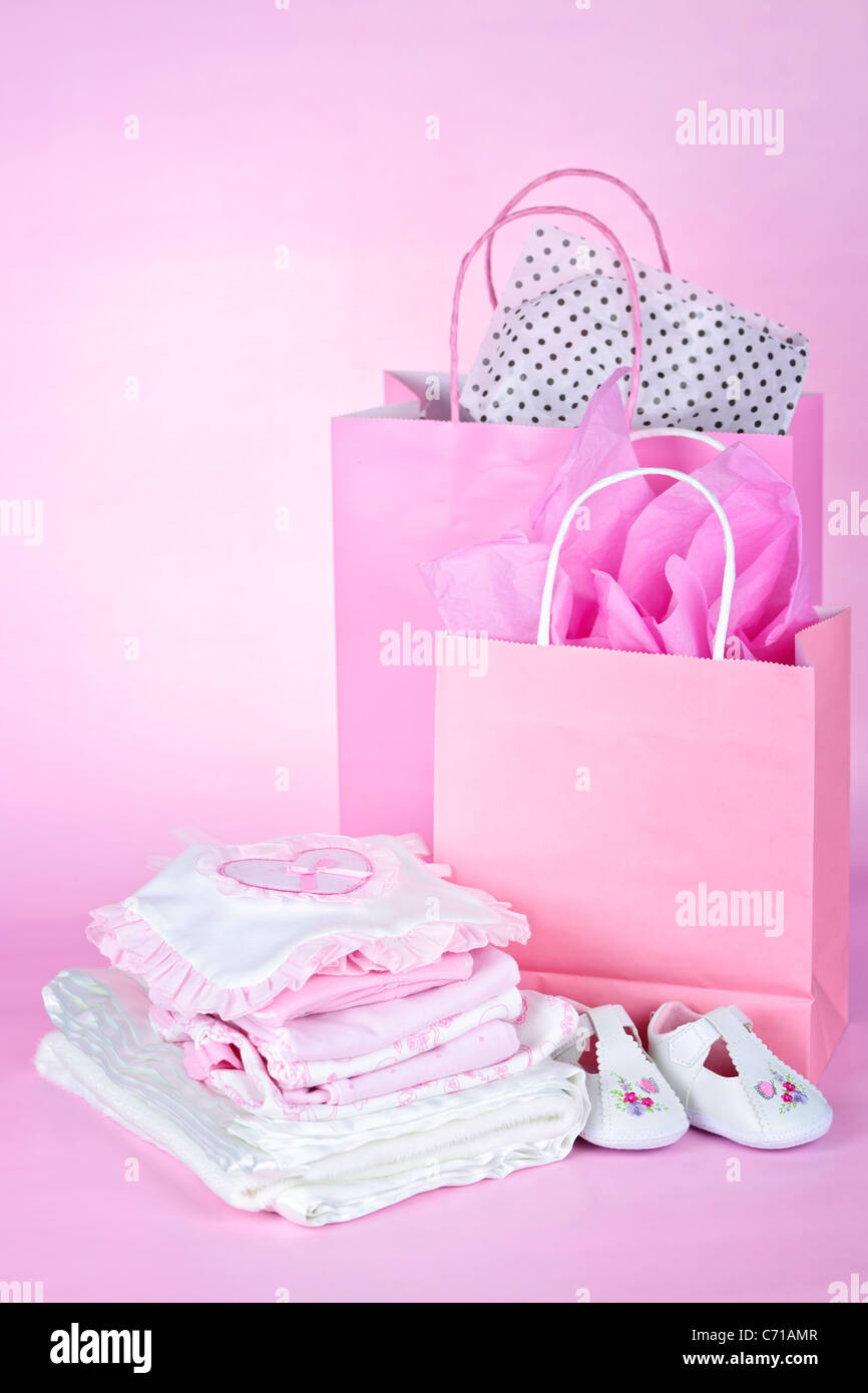 Gift bags and infant clothes for girl baby shower on pink background - Stock Image