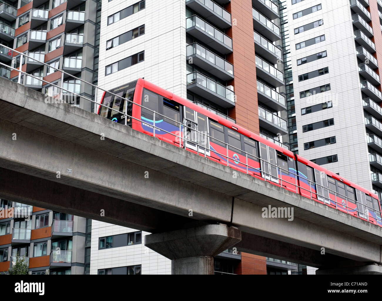 A train on the Docklands Light Railway passes new apartment blocks near East India DLR station on Blackwall Way, - Stock Image