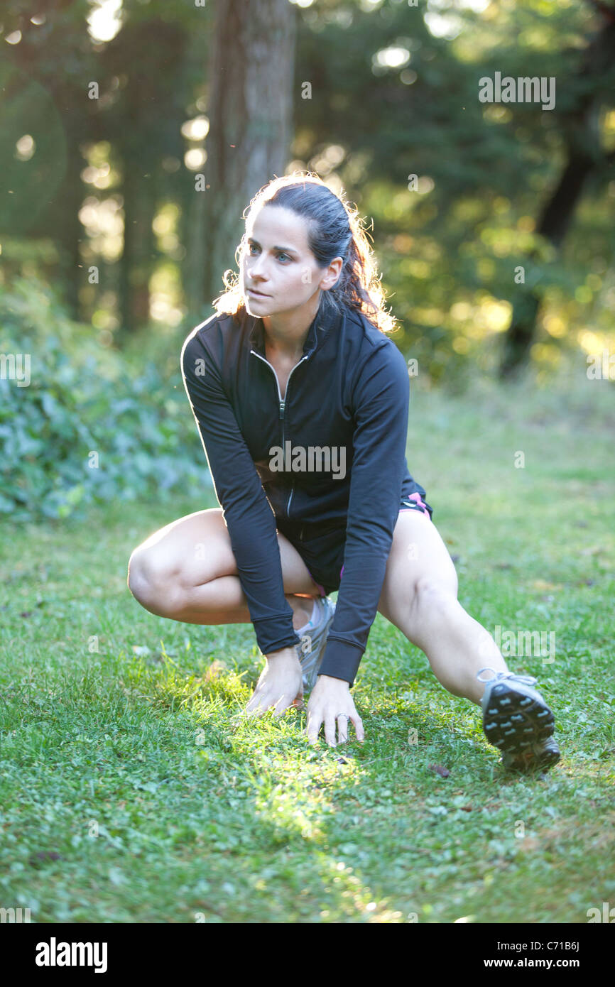 A young woman stretches before a run at Point Defiance Park. - Stock Image