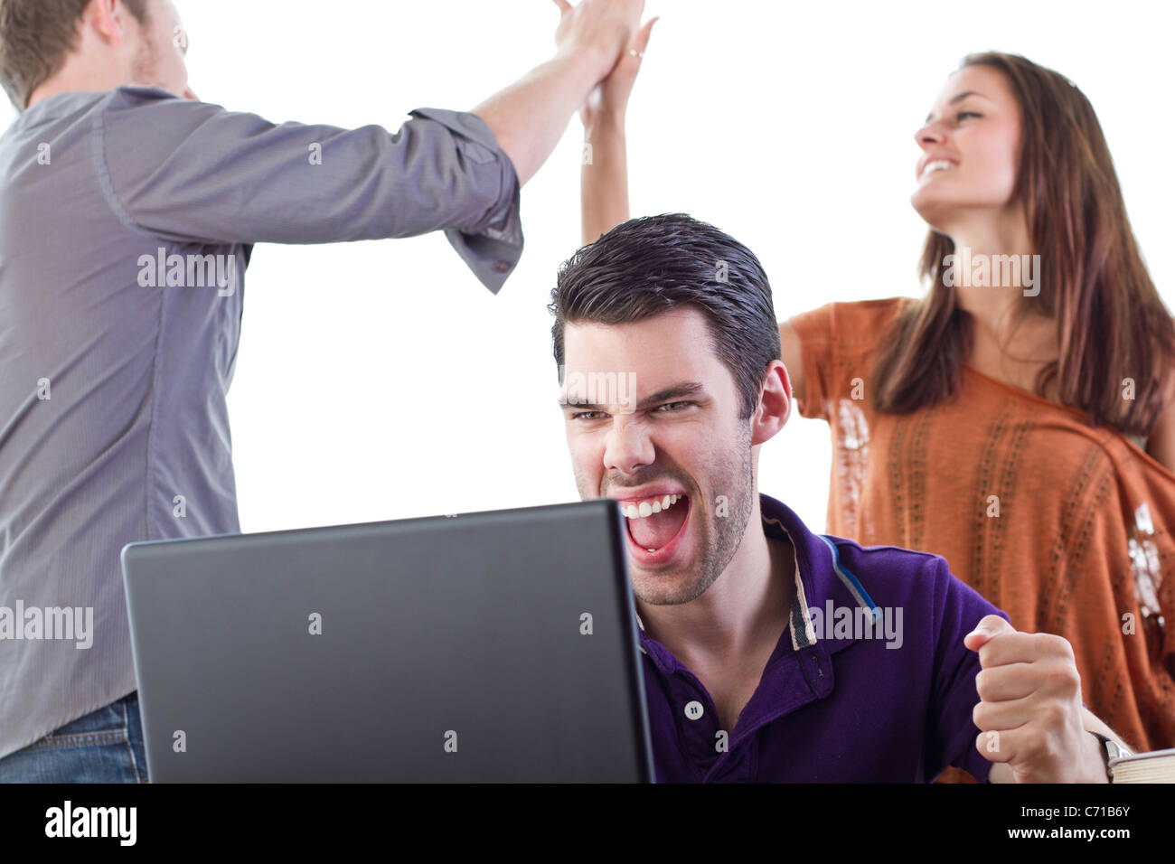 Three happy 20 somethings react to some fantastic news - Stock Image
