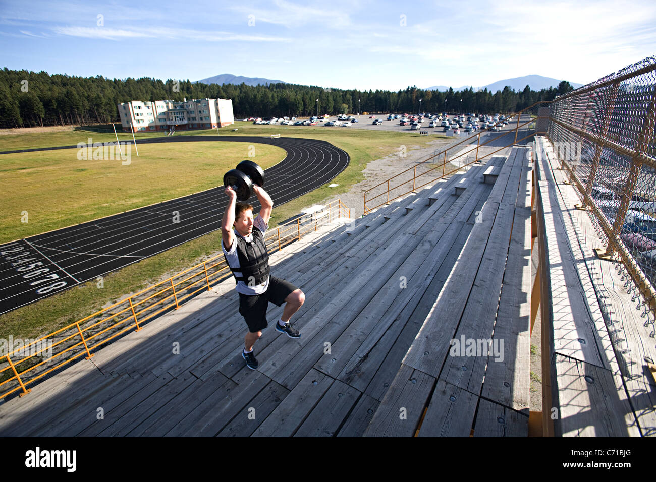 man in shorts running stairs with weighted vest and weight held above head - Stock Image