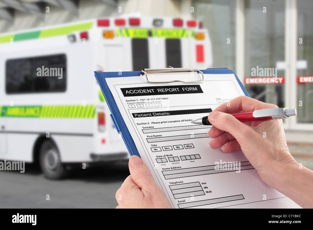 Hand Completing an Accident Report Form by Ambulance - Stock Image