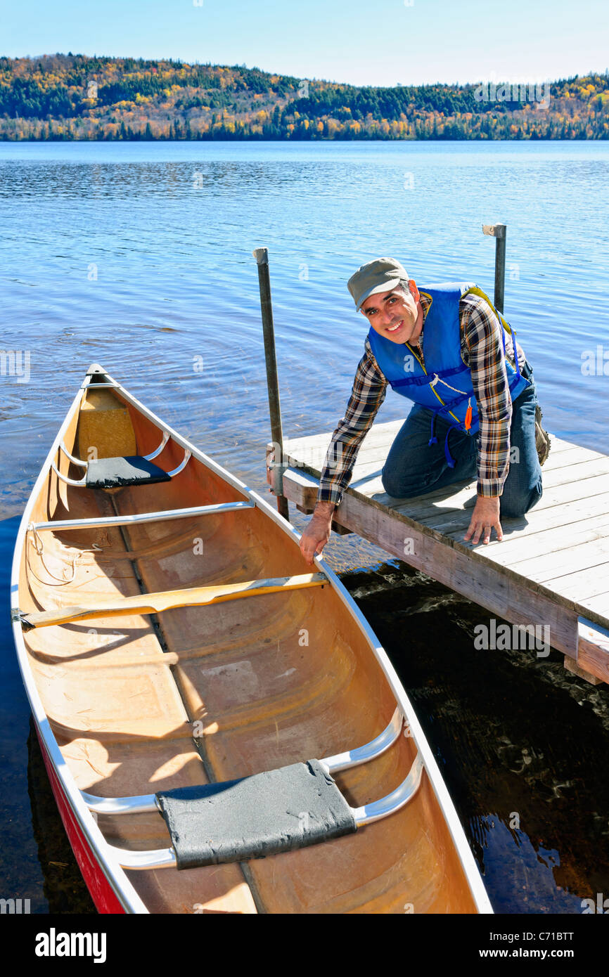 Man holding canoe at dock on Lake of Two Rivers, Ontario, Canada - Stock Image