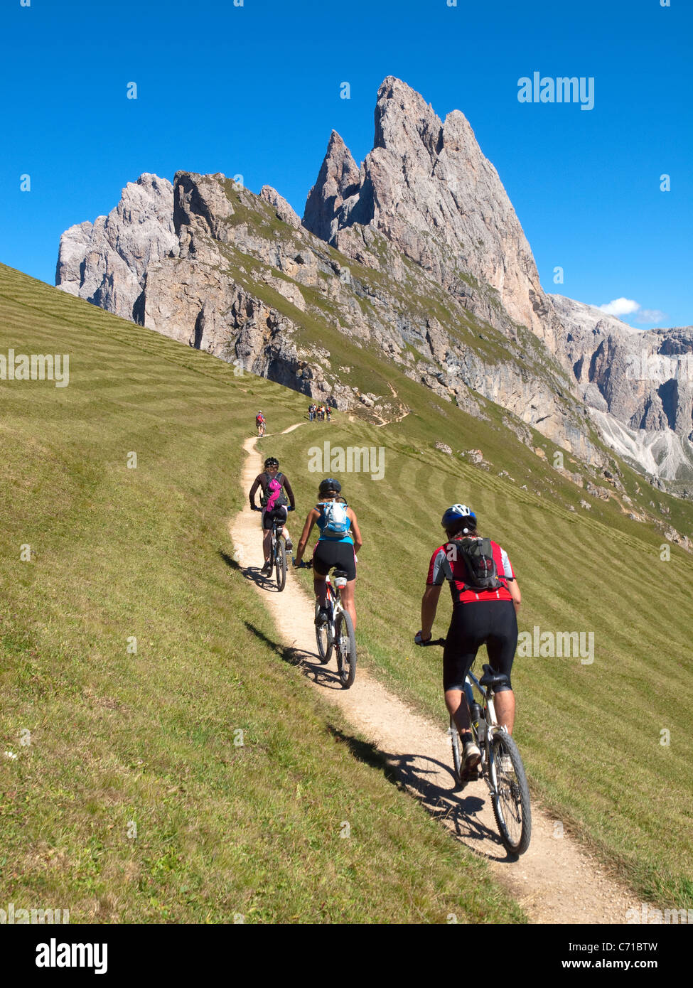Three mountain bikers are riding a small single trail high in the mountains, with a rock cliff in the background - Stock Image