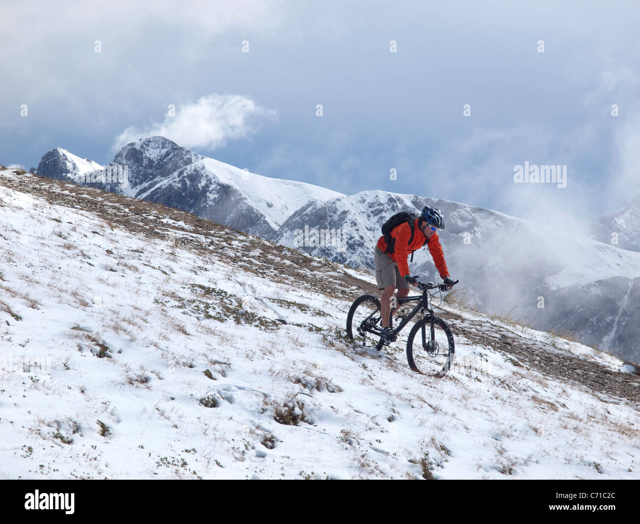 A mountain biker rides through the snow at Kronplatz, mountains and clouds in the background. - Stock Image