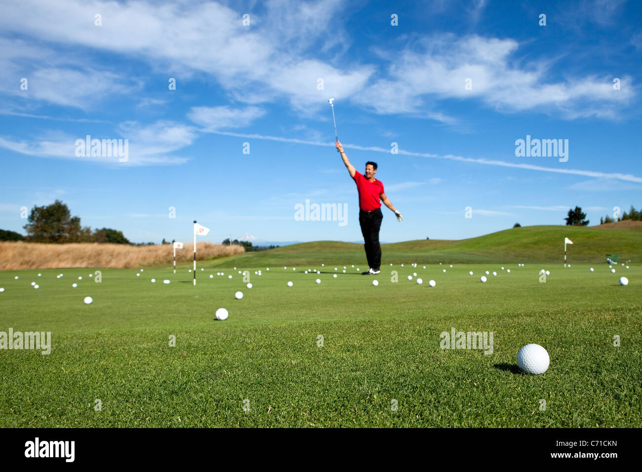 Man excited about making a putt while golfing. - Stock Image