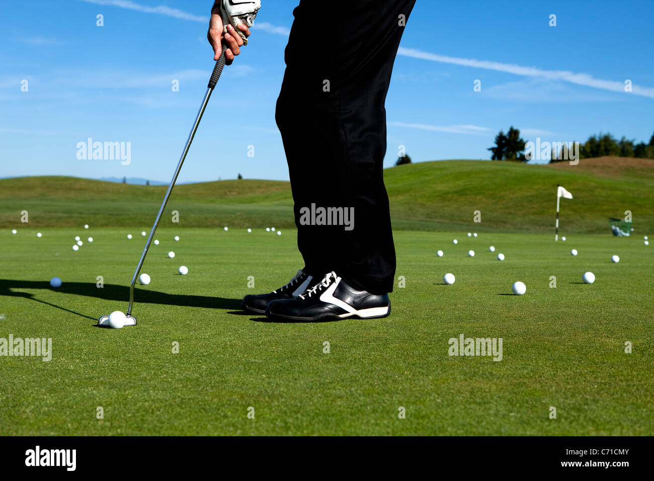Man lining up a putt while golfing. - Stock Image
