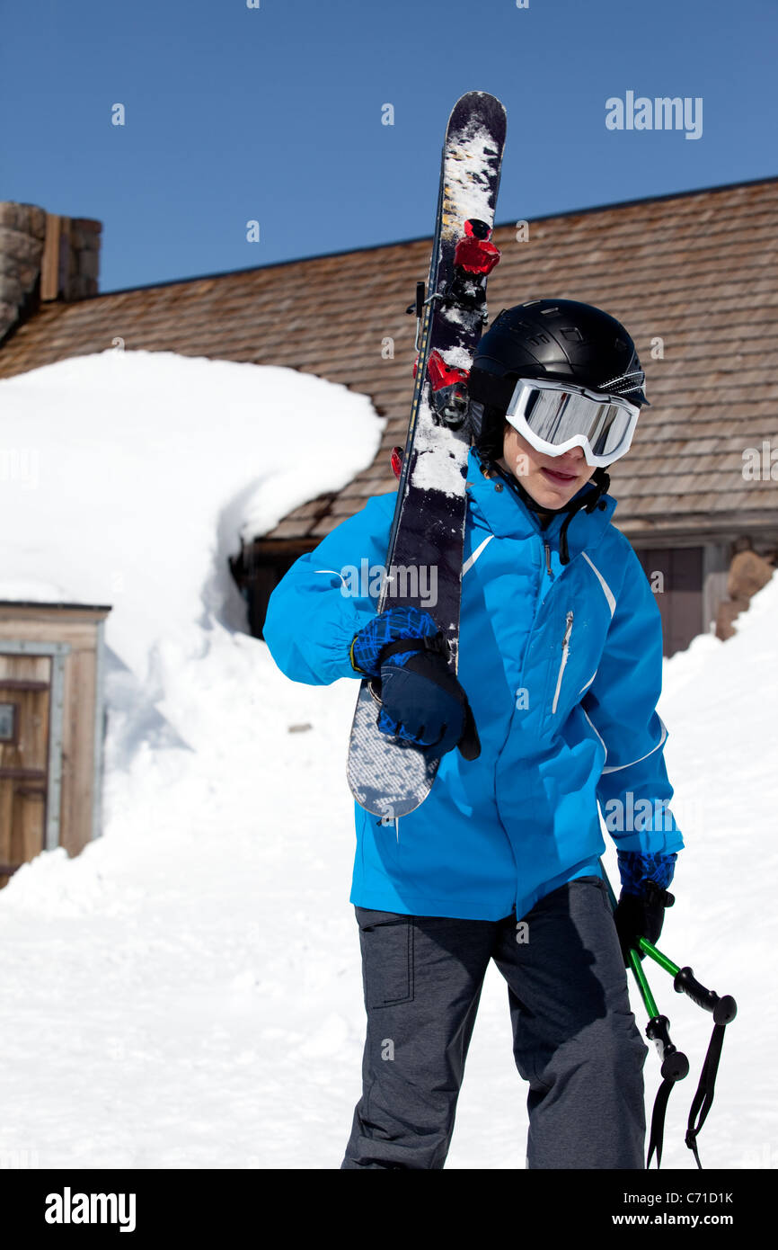 Young boy carrying ski's. - Stock Image