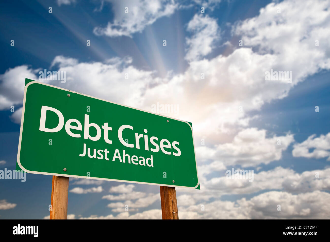 Debt Crises Green Road Sign Against Dramatic Sky, Clouds and Sunburst. - Stock Image