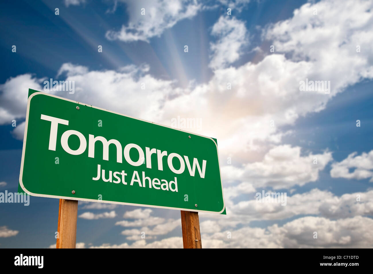 Tomorrow Green Road Sign Against Dramatic Sky, Clouds and Sunburst. - Stock Image