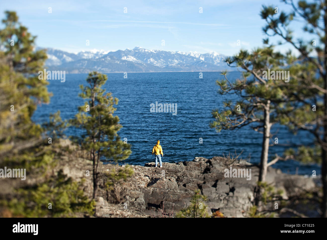 A athletic retired man stands at the edge of a cliff overlooking a beautiful lake in Idaho. - Stock Image
