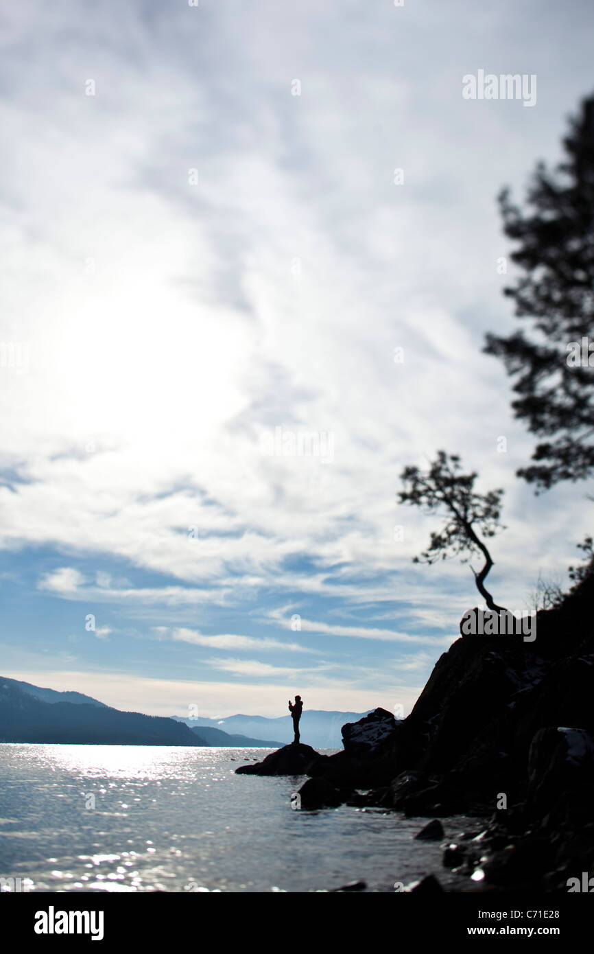 A male figure stands meditating on a rock with glimmering water in Idaho. - Stock Image