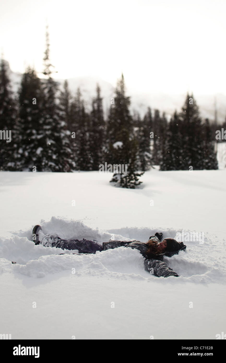 A beautiful women smiles while making a snow angel in a pristine field at sunset in Wyoming. - Stock Image