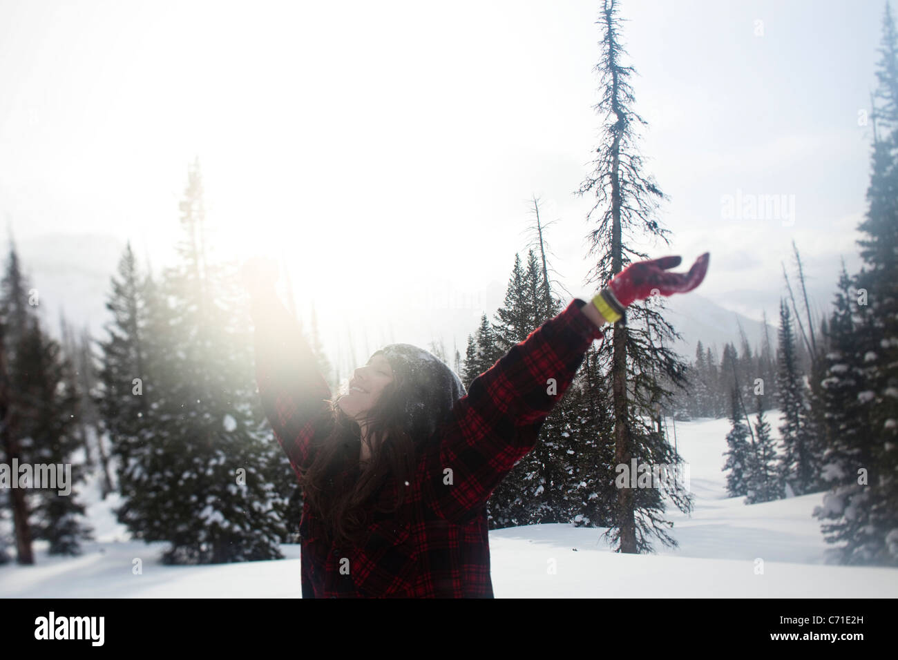 A beautiful women smiles while hiking through a pristine snow field at sunset in Wyoming. - Stock Image