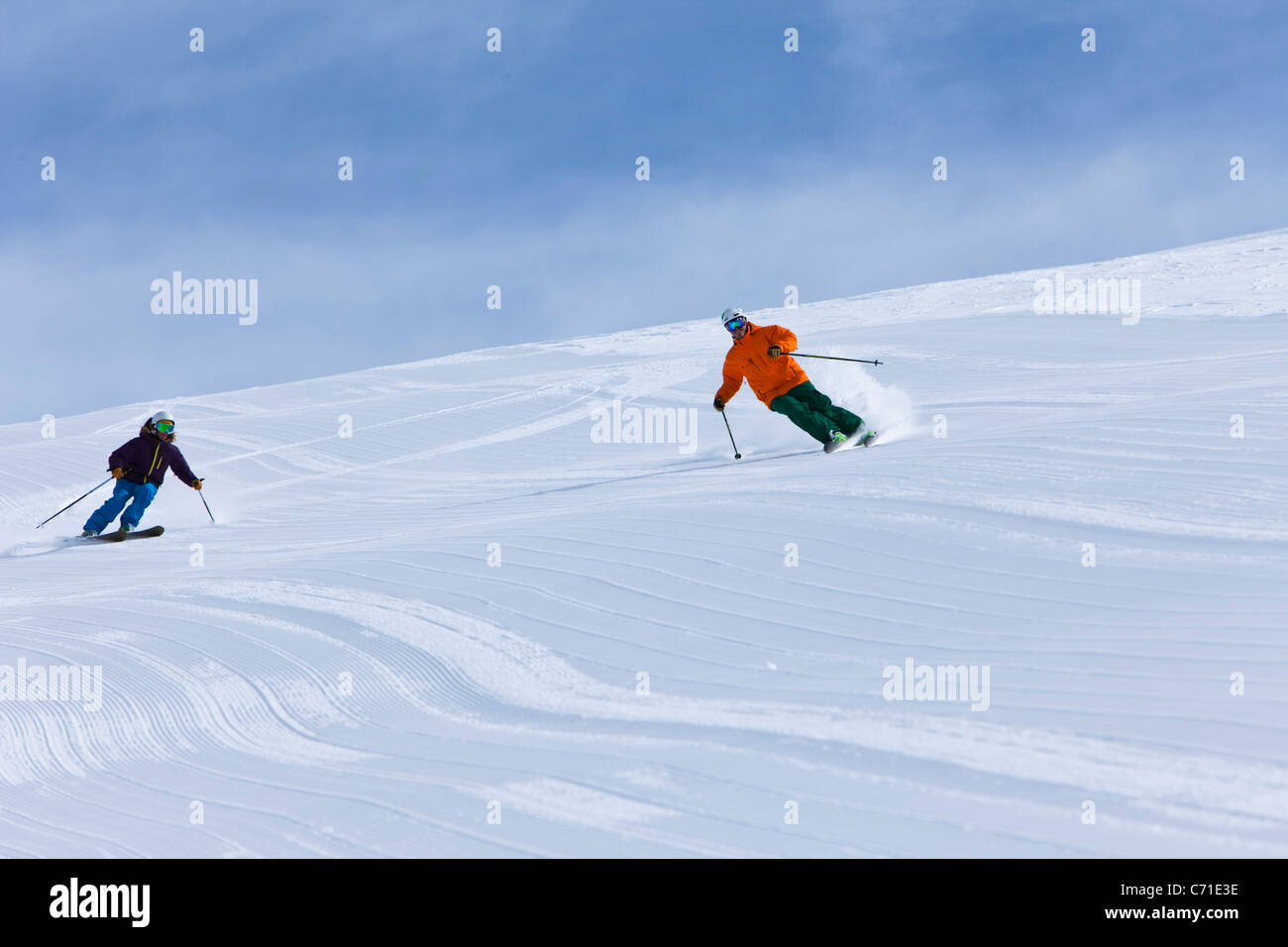 A male and female alpine skier link groomer turns on sunny day in Colorado. - Stock Image