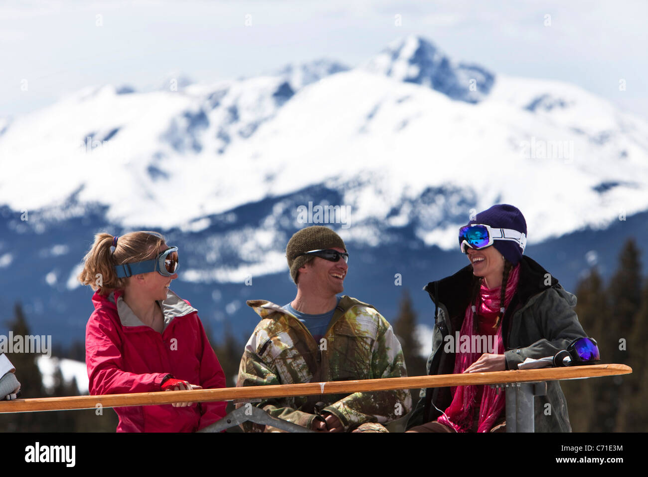 Three friends laugh and smile while enjoying a fun ski day in Colorado. - Stock Image