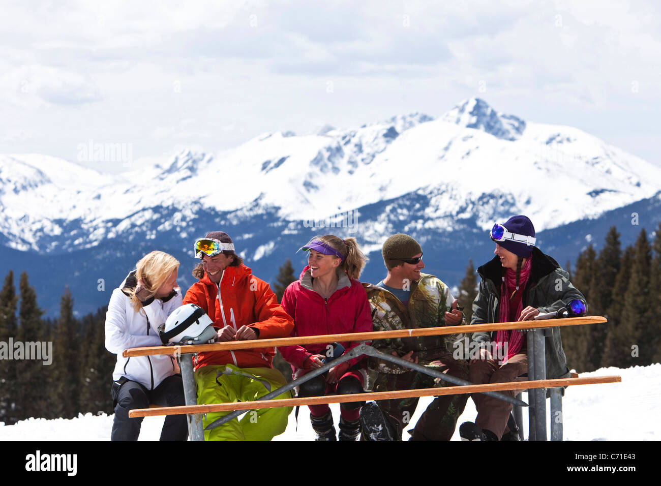 A large group of friends smile and laugh while enjoying a beautiful skiing day in Colorado. - Stock Image
