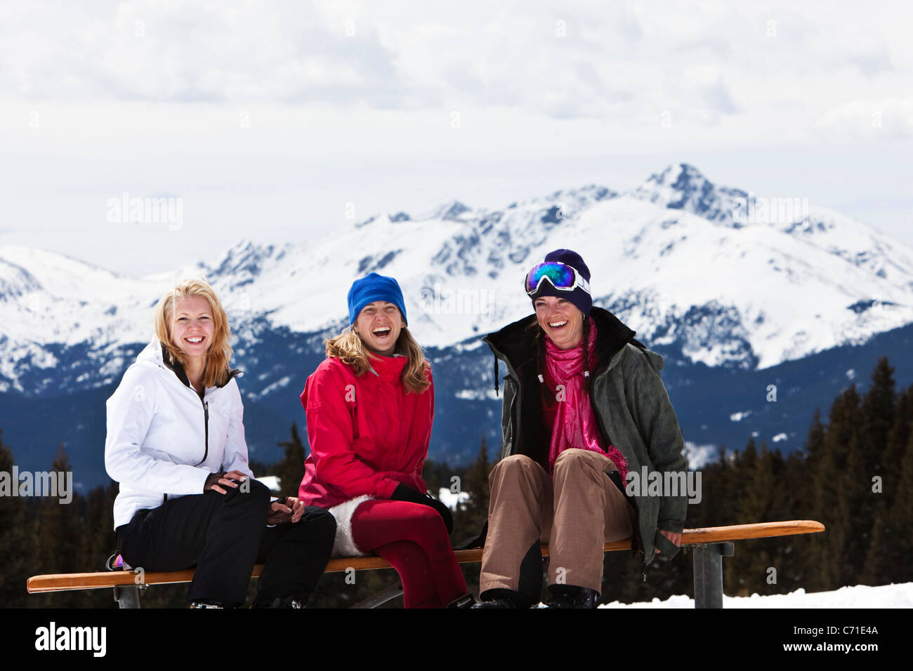 Three beautiful women laugh and smile while enjoying a fun ski day in Colorado. - Stock Image