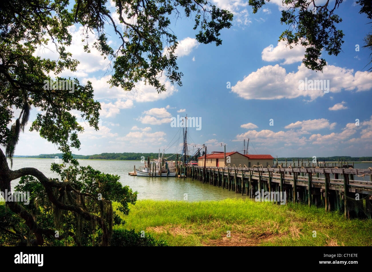 Shrimp boats are docked at the end of a pier on the Intracoastal Waterway on Hilton Head Island, SC. - Stock Image