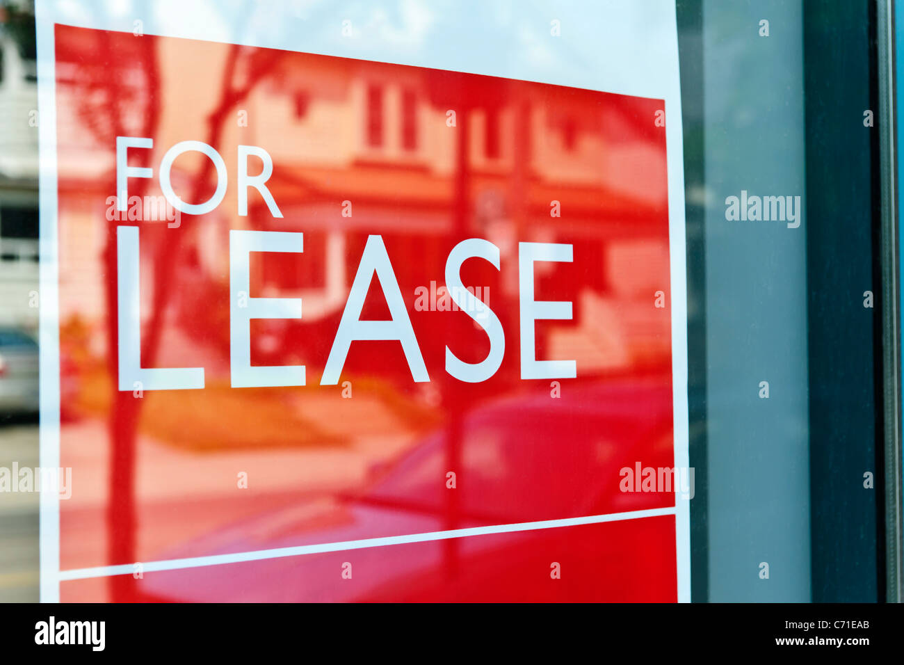 For Lease sign on red in window reflecting street scene - Stock Image
