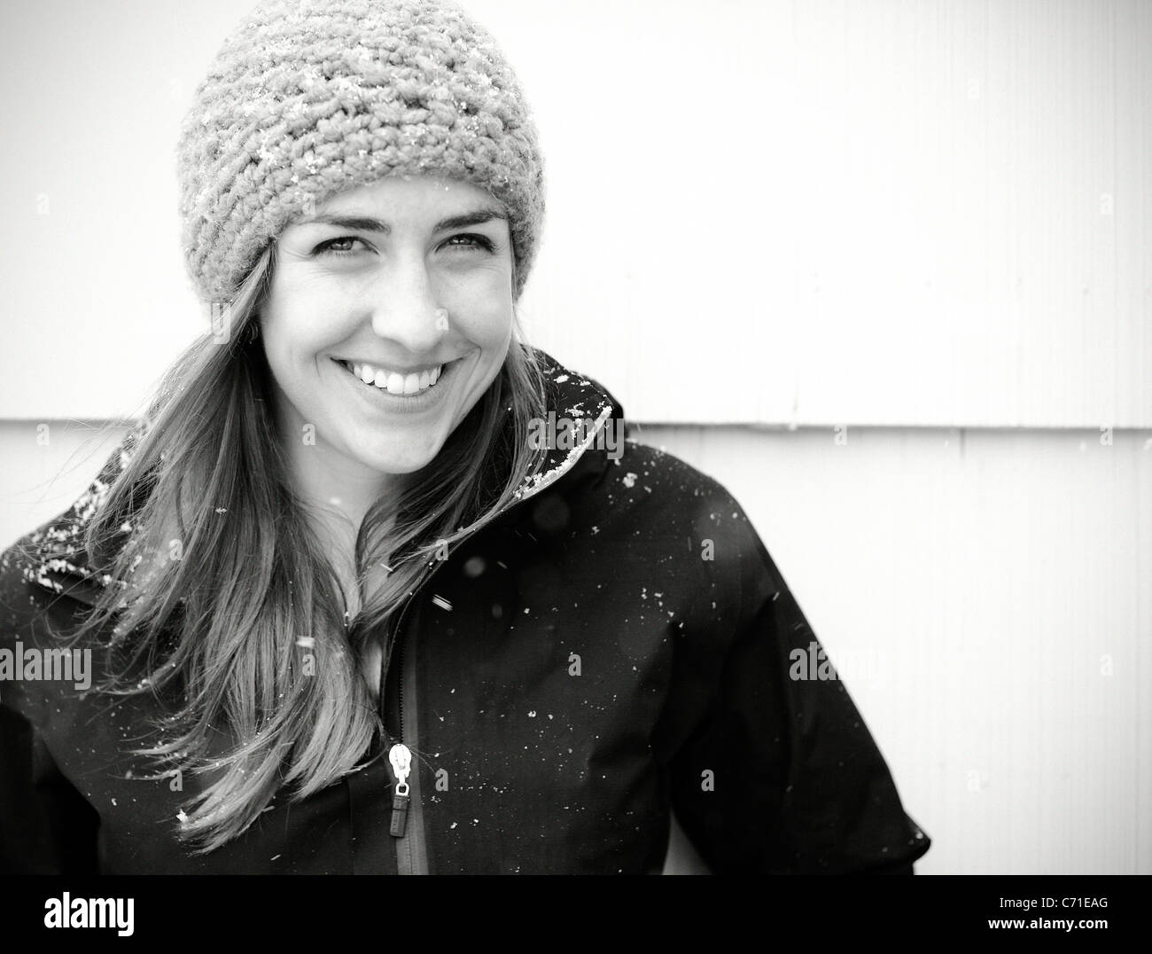 A woman with a hat smiles. - Stock Image