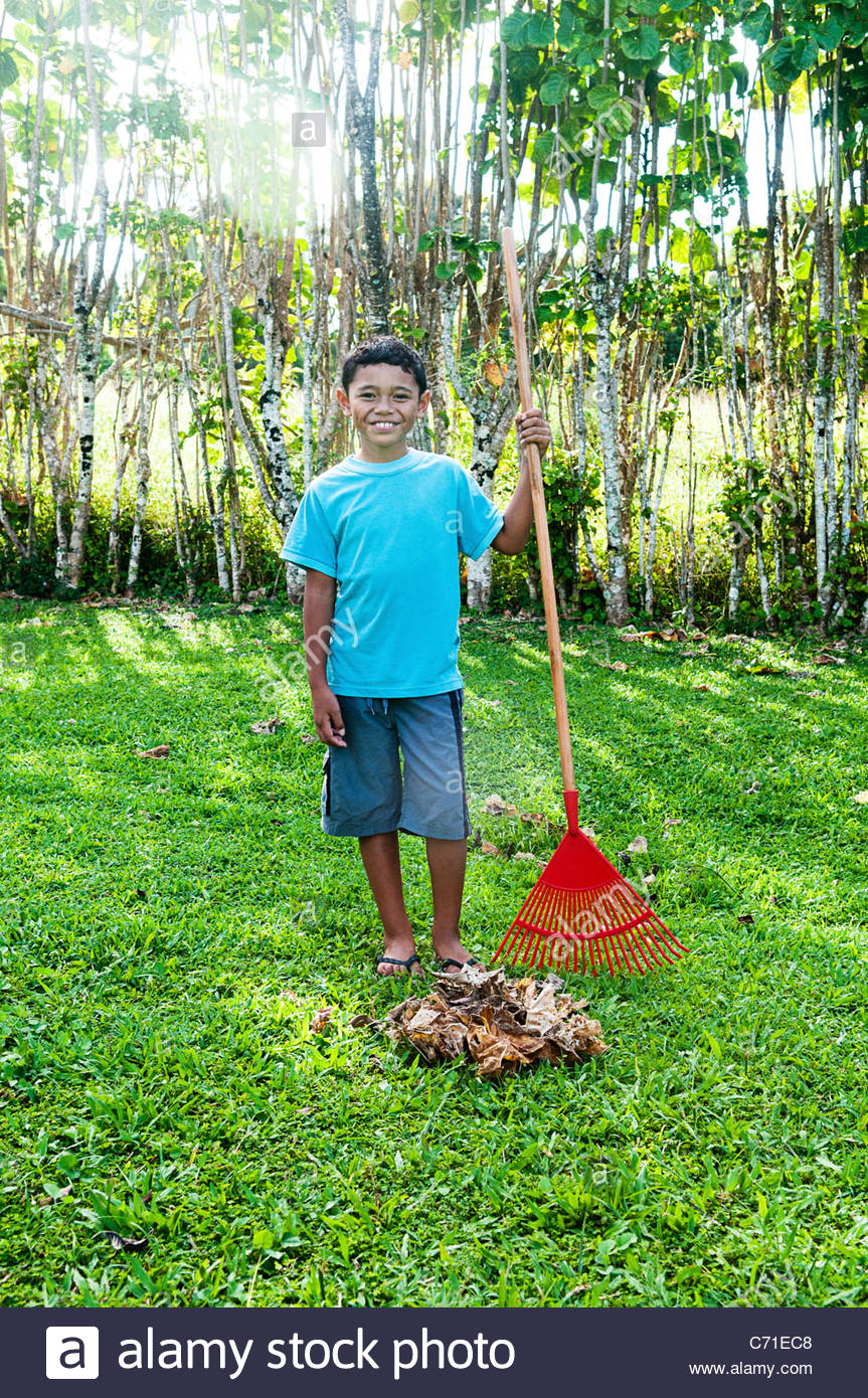 Boy standing next to a pile of raked leaves, Cook Islands. - Stock Image