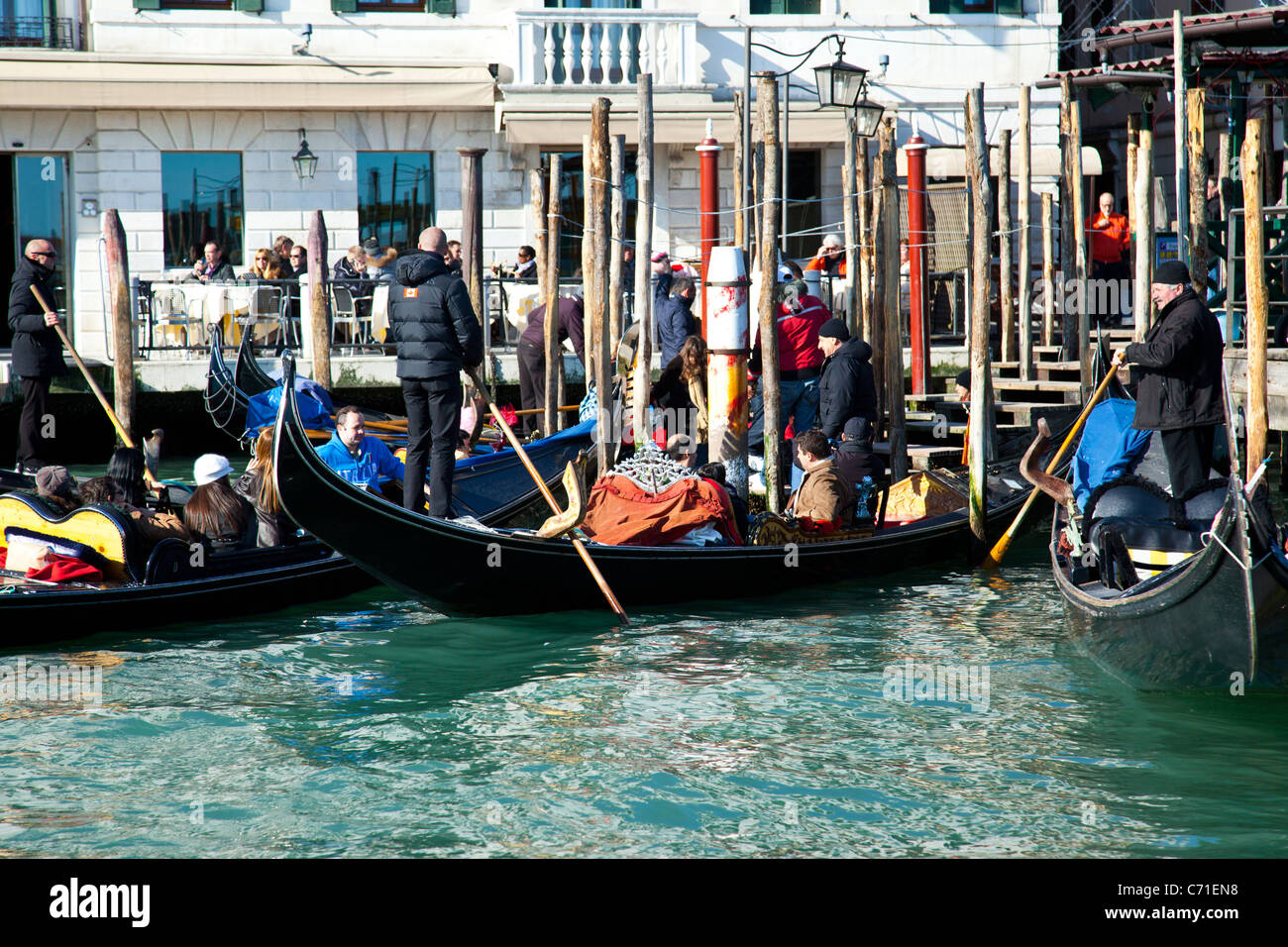 Gondolas picking up tourists by the Grand Canal in Venice Italy. - Stock Image