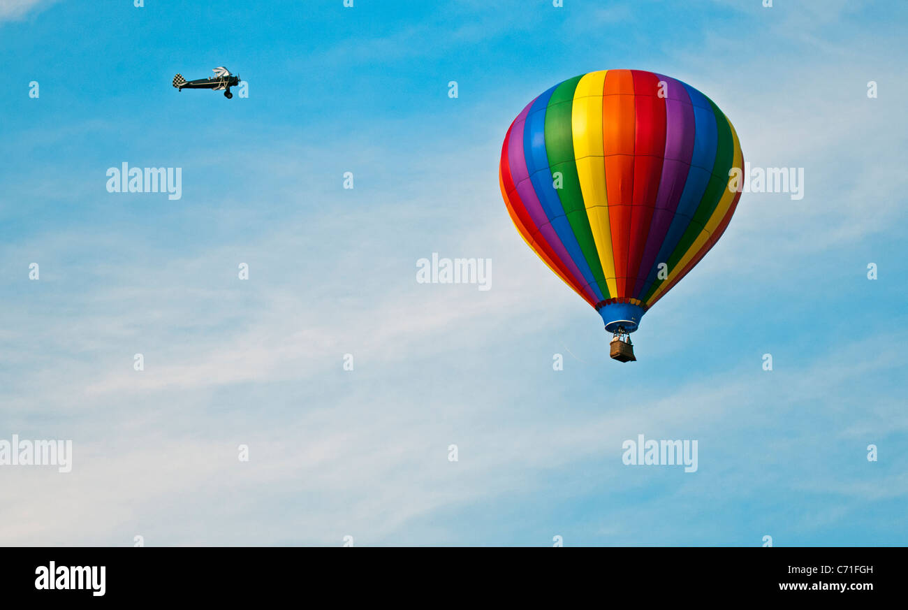 Bealeton, Virginia / One hot air balloon flying with a single engine biplane performing aerial acrobatics around - Stock Image