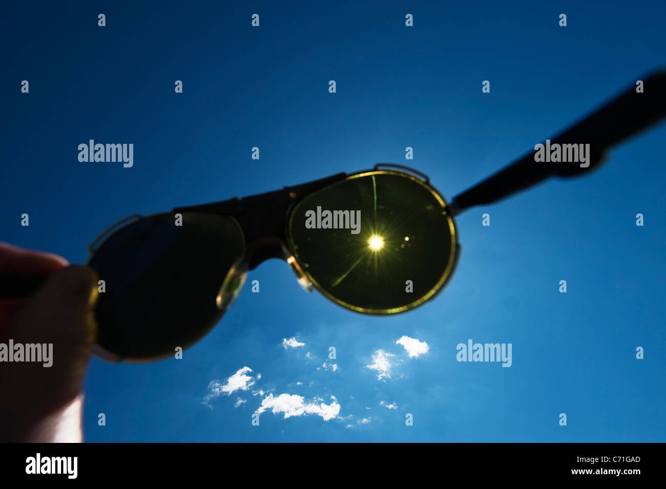 ea69b93d29e Hand holding strong glacier sunglasses up to the sun against a blue sky  with puffy white