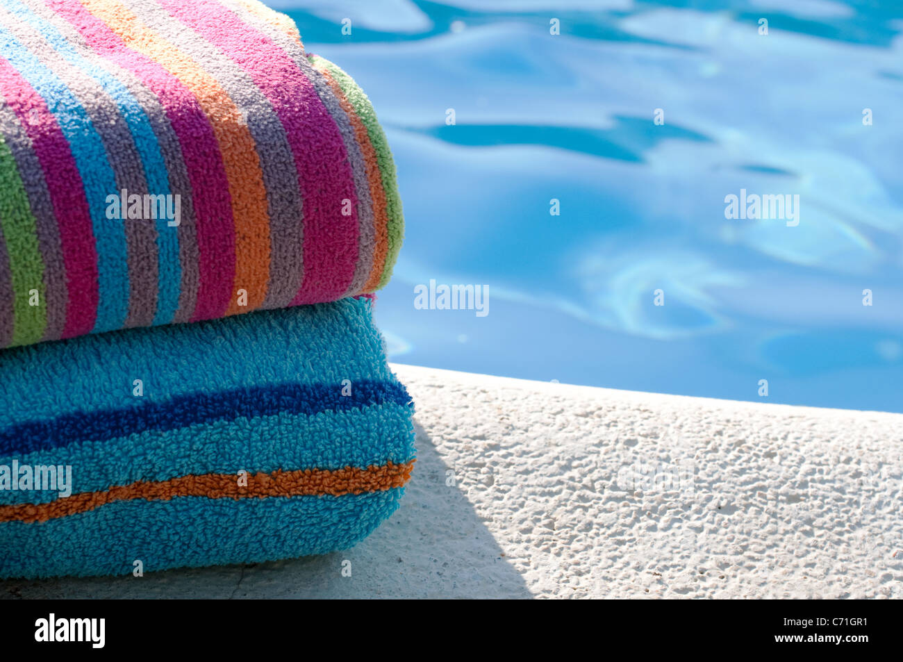 Colourful towels folded by pool - Stock Image