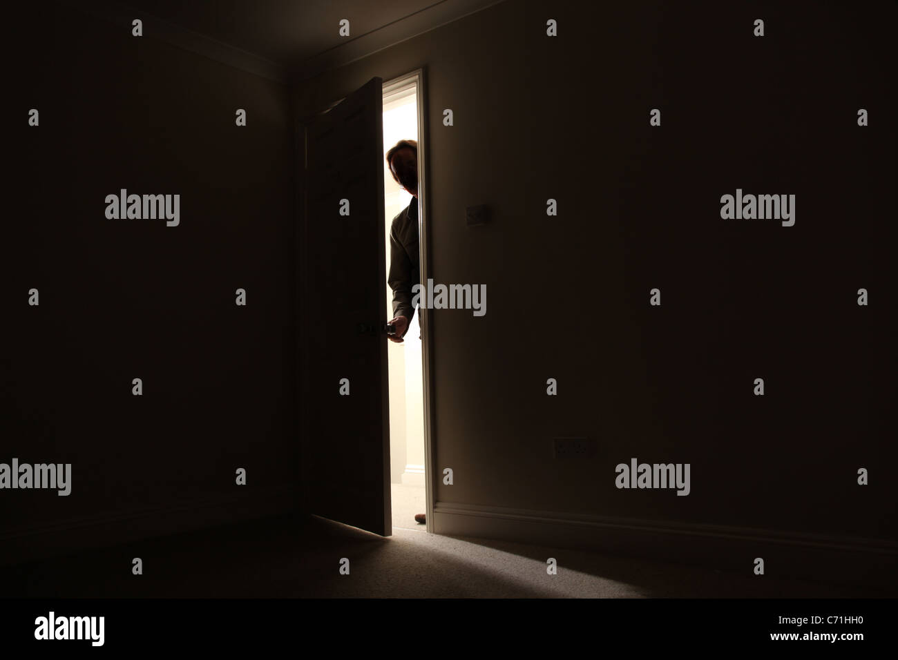 Silhouette of a male standing outside a dark room looking in. - Stock Image
