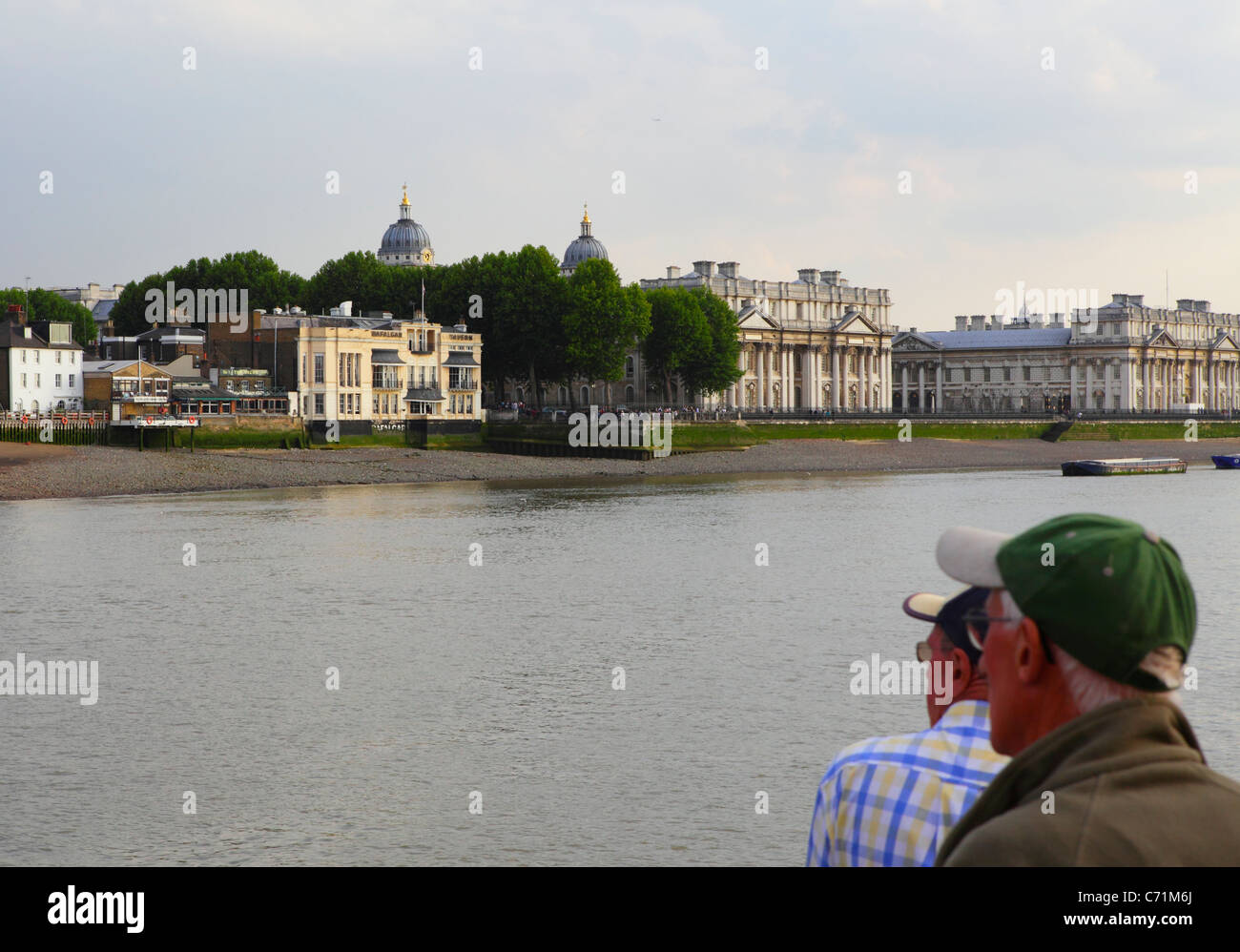 Tourists on River Thames Cruise looking across to the Trafalgar Tavern and Greenwich Maritime Museum, East London, - Stock Image