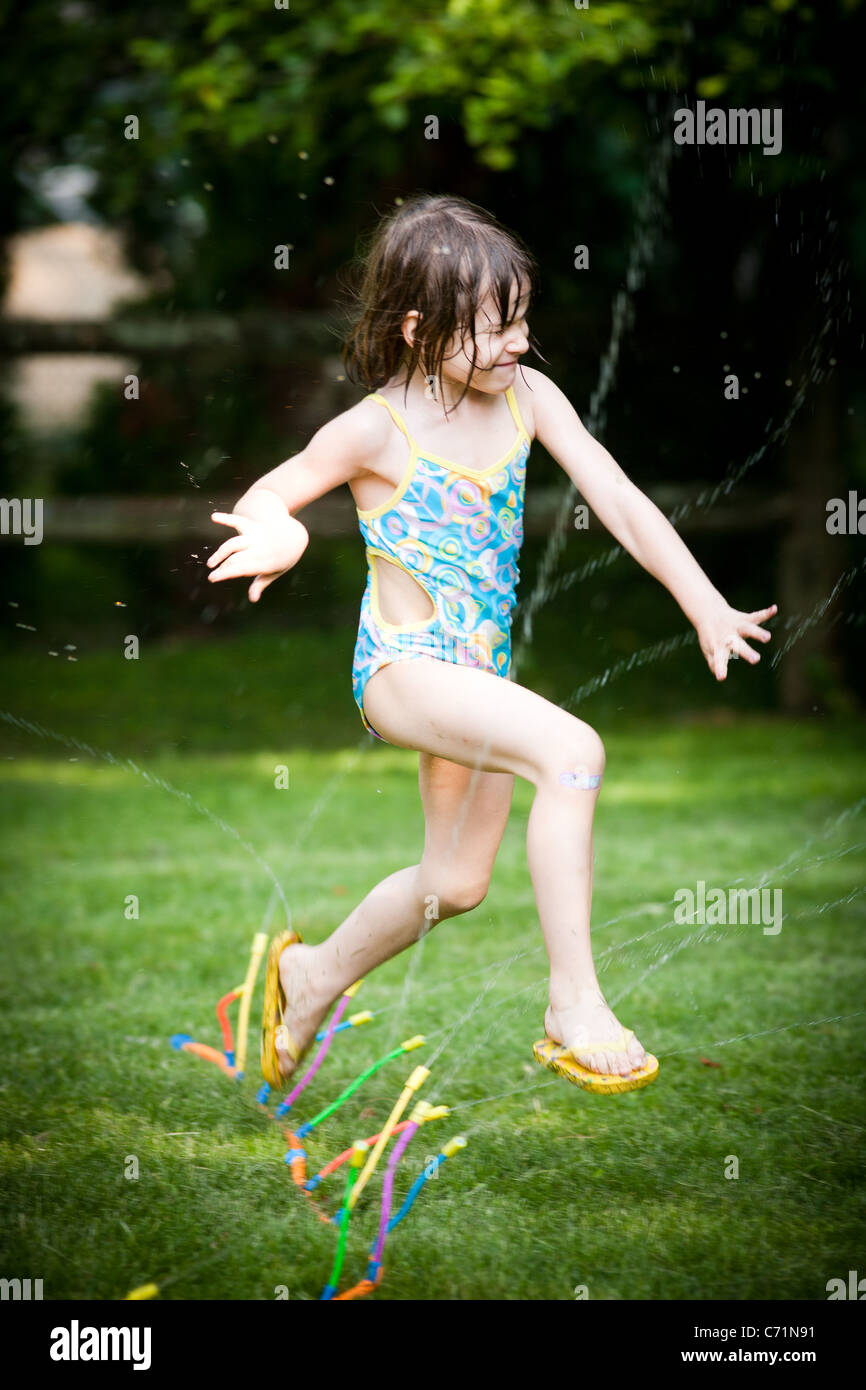 A five-year-old girl jumps through a sprinkler in her bathing suit in her back yard. - Stock Image
