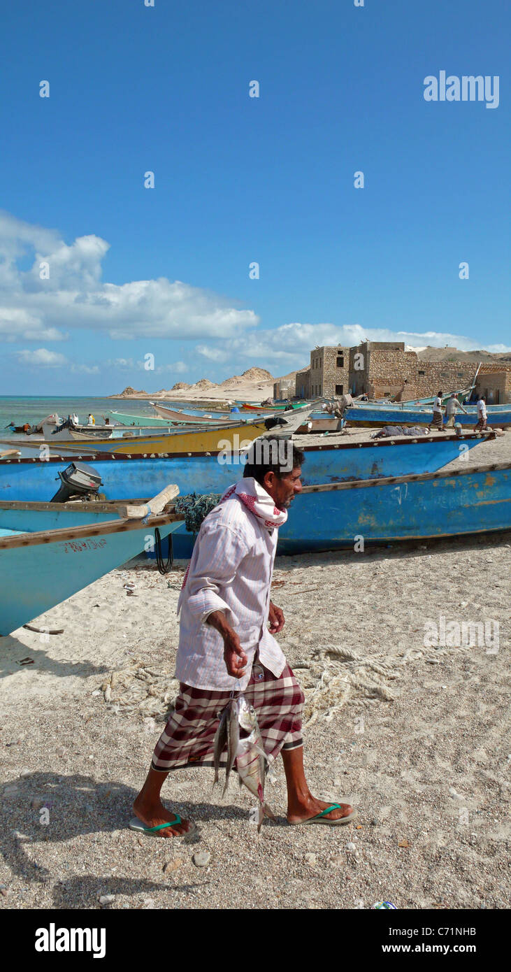 A man carries fish purchased at the fish market on the beach in Qalansiyah, Socotra, Yemen. - Stock Image