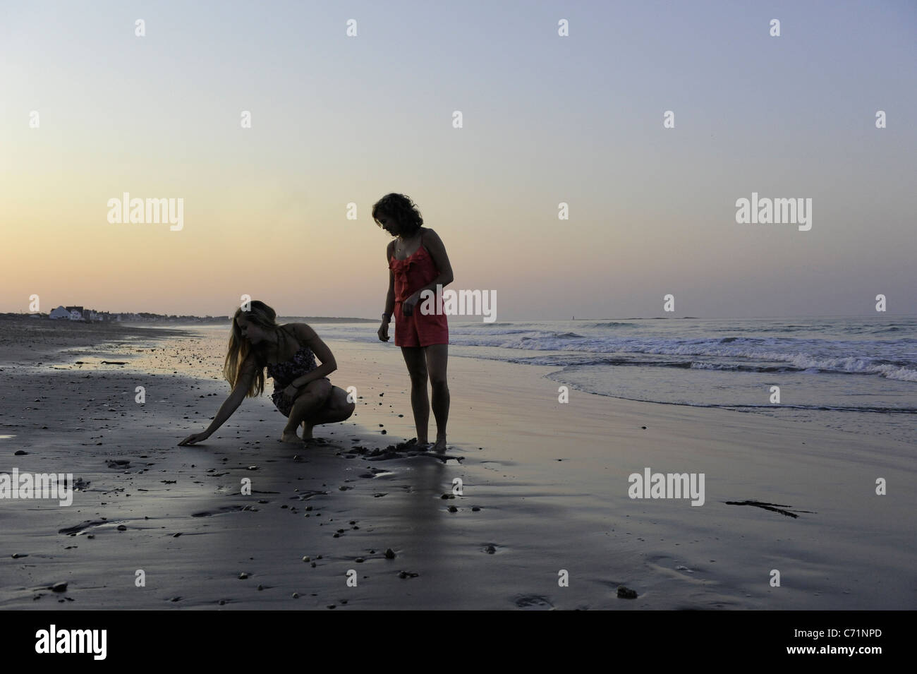 Two young women search for shells at sunset on the beach. - Stock Image