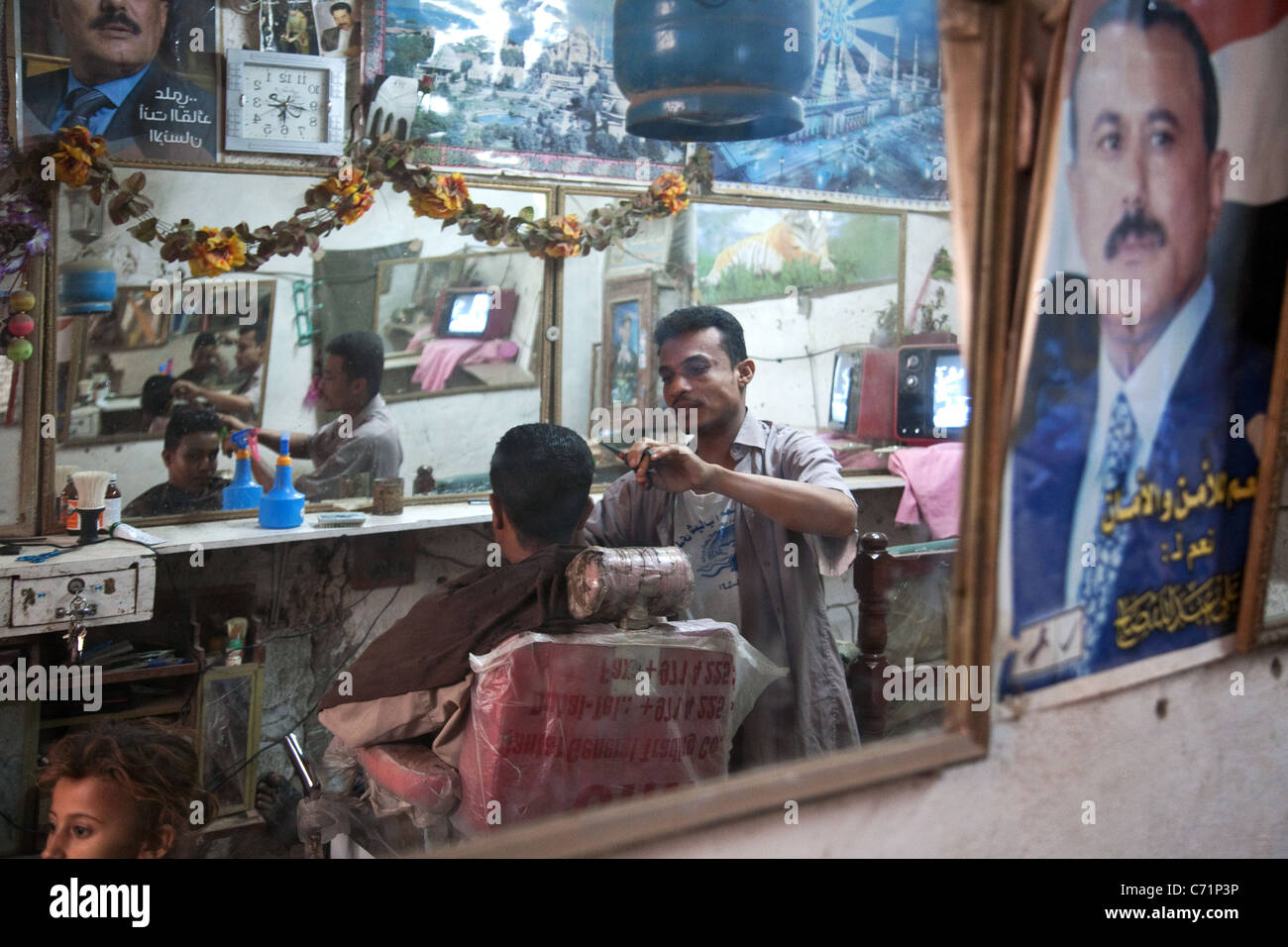 Interior of a barber shop with mirrors and the poster of the  president Ali Abdullah Saleh in Zabid, Yemen. - Stock Image