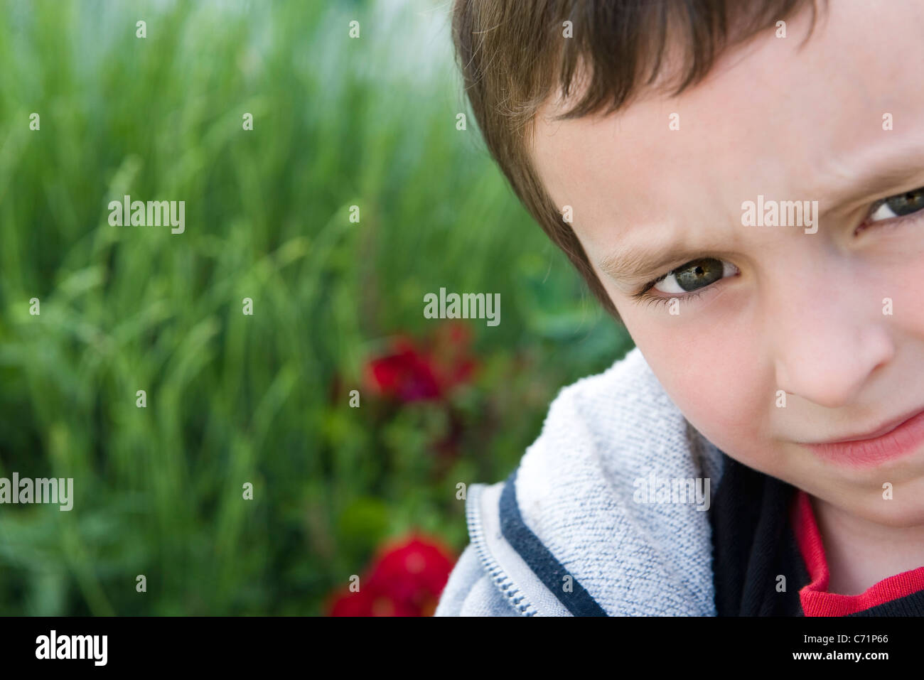Boy looking at camera with furrowed brow, portrait - Stock Image