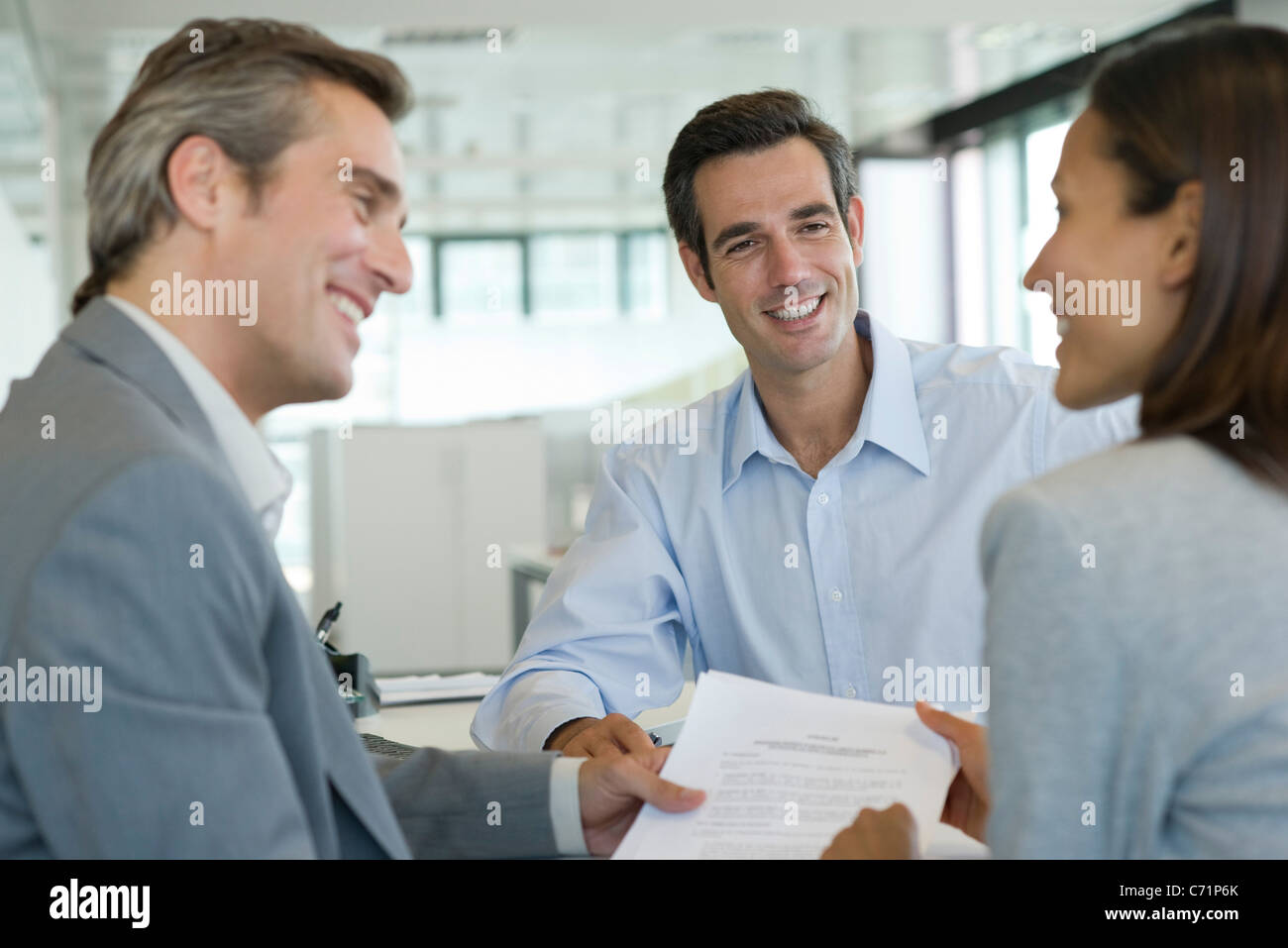 Smiling couple discussing contract with adviser - Stock Image