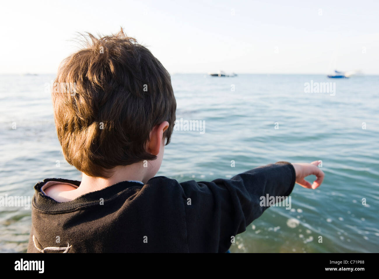 Boy looking at ocean view, pointing - Stock Image