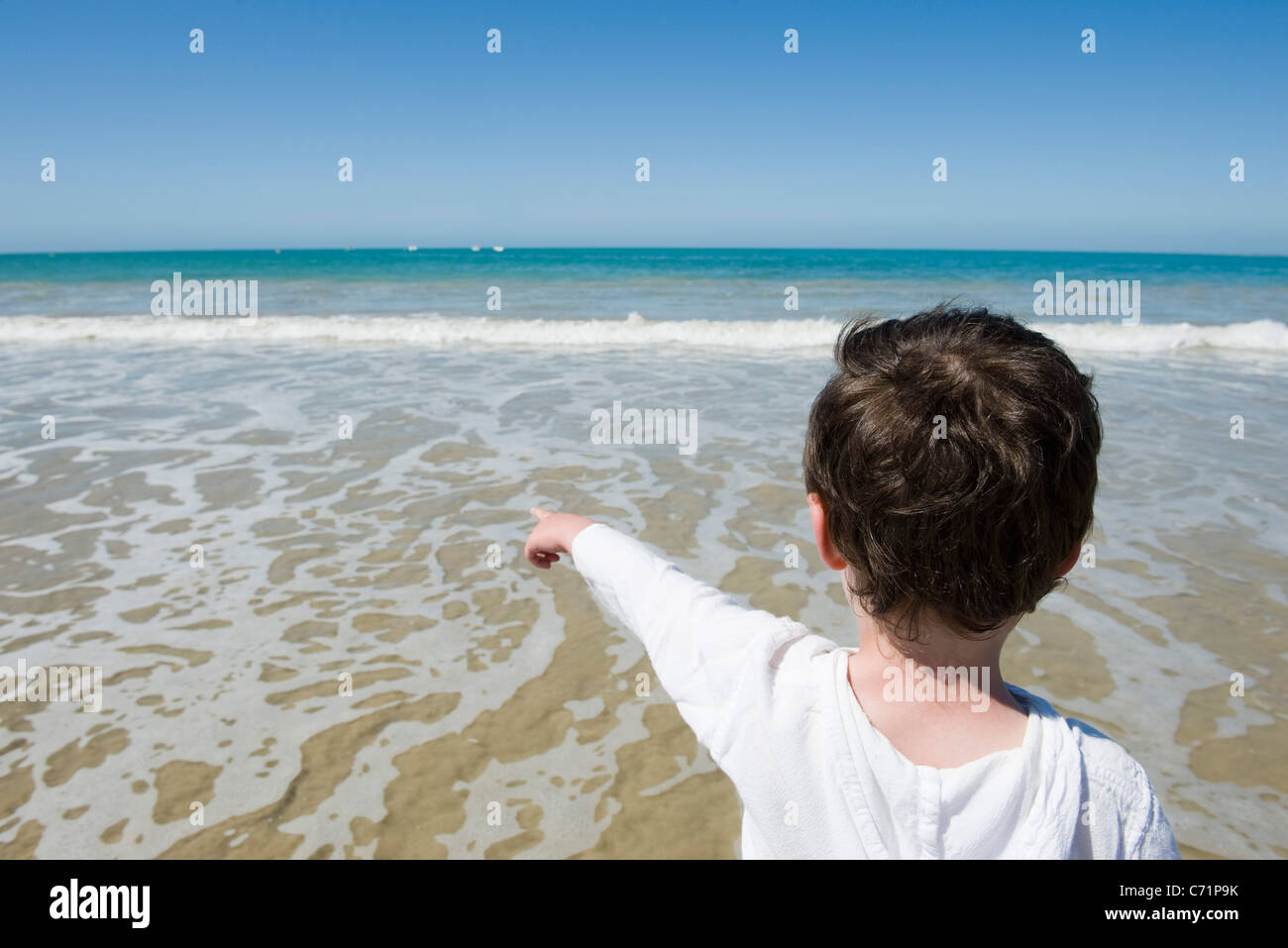 Little boy at the beach, pointing at sea, rear view - Stock Image