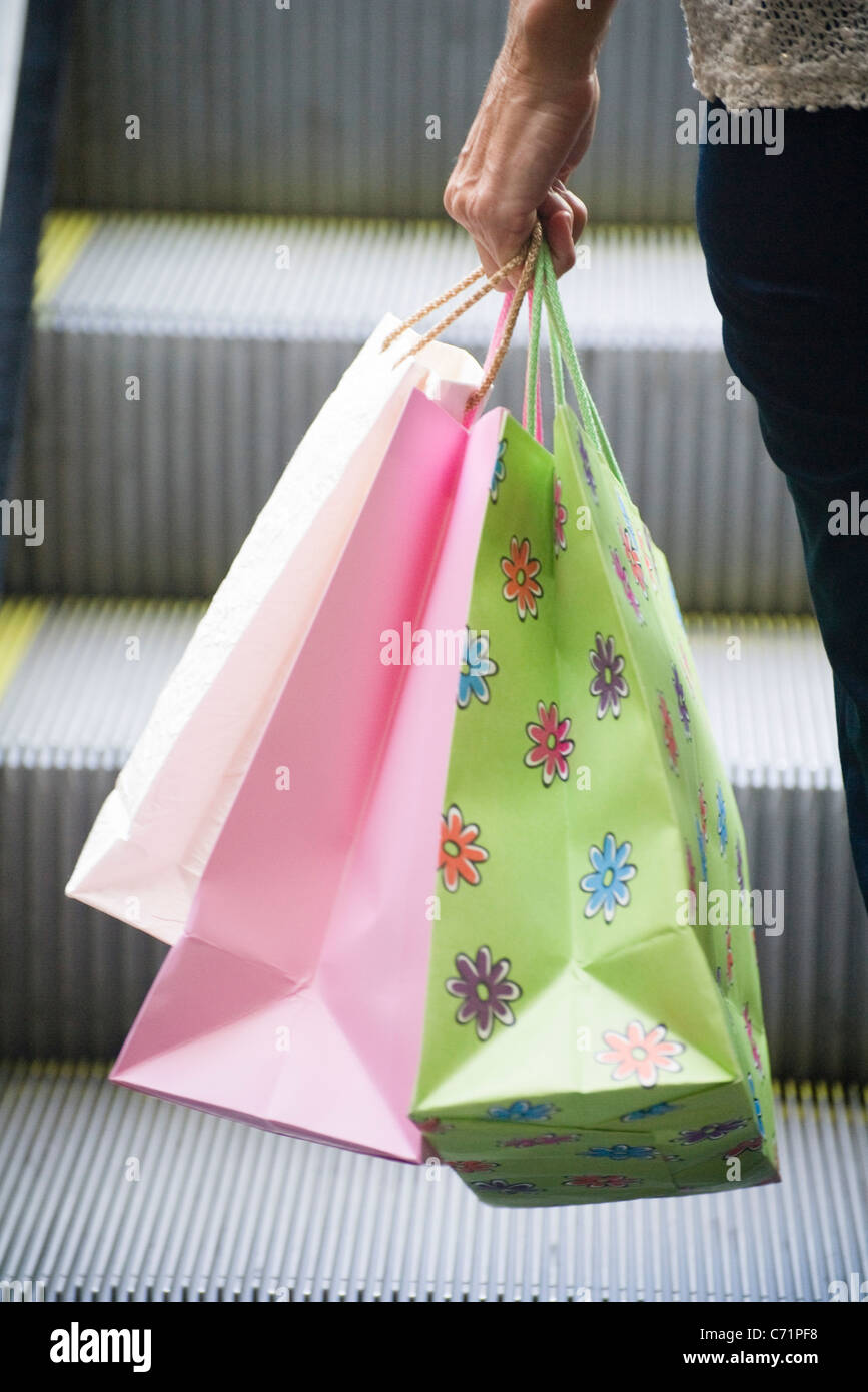 Person carrying shopping bags - Stock Image