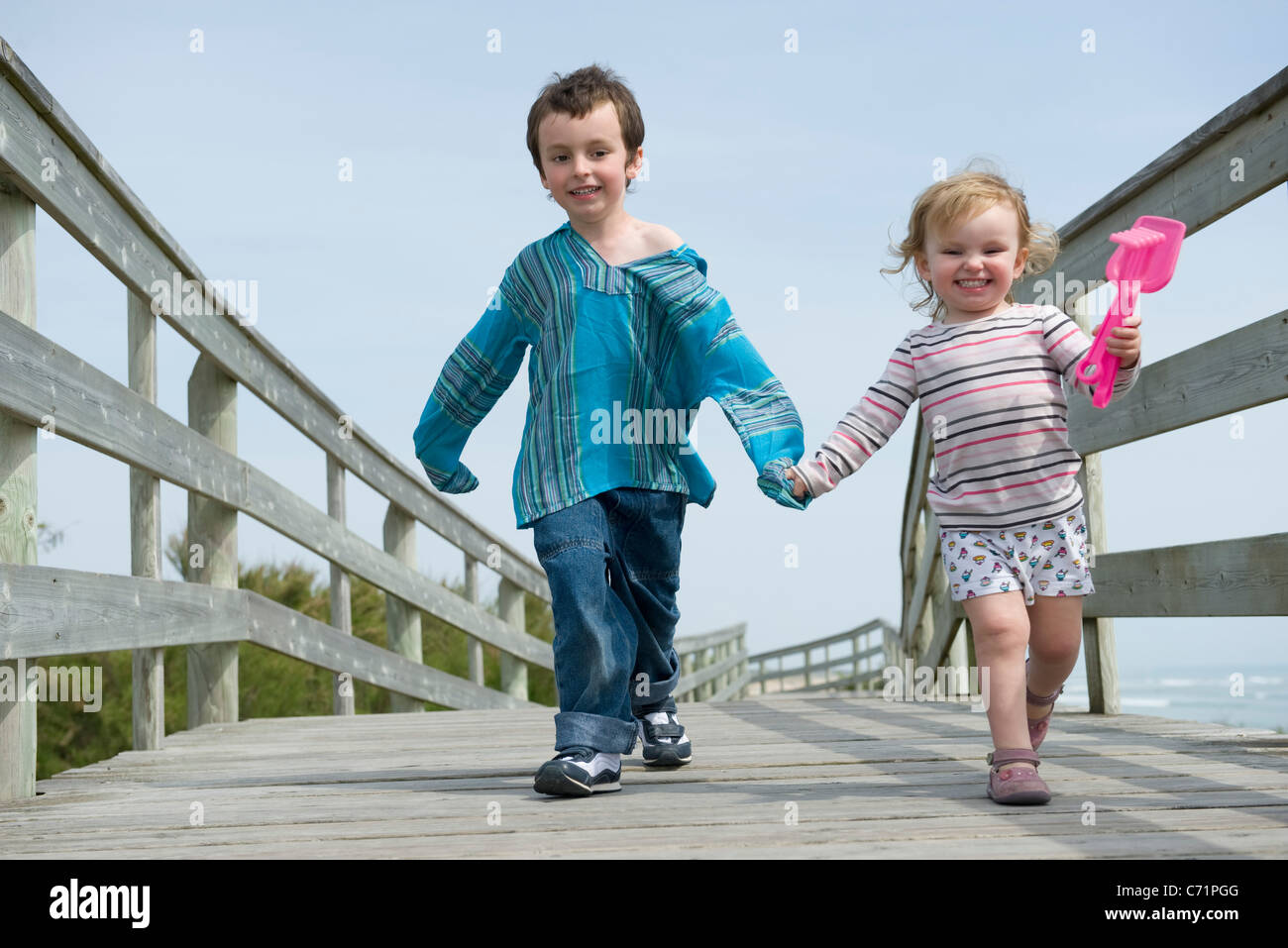 Young siblings walking hand in hand on boardwalk Stock Photo