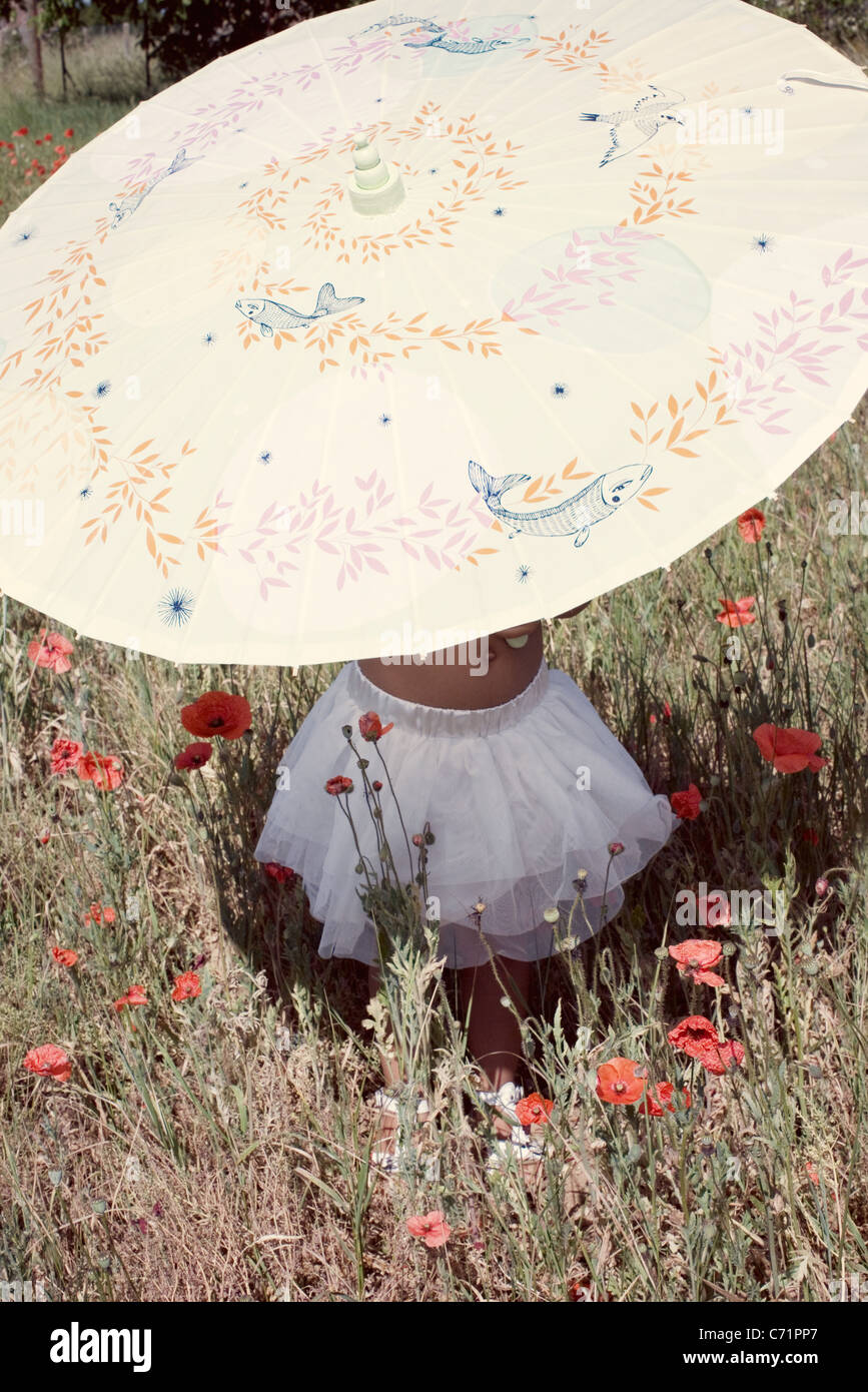 Little girl with parasol in meadow, mid section Stock Photo