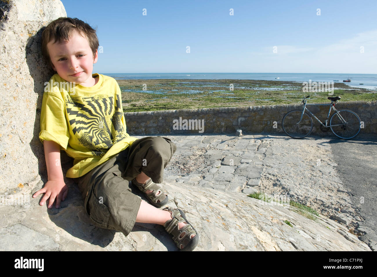 Boy leaning against stone wall, portrait - Stock Image