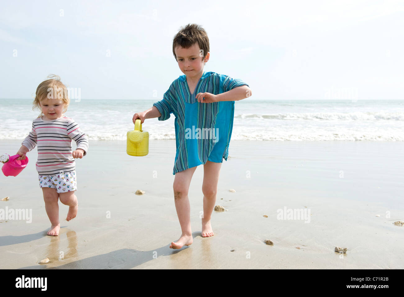 Young siblings walking on wet sand at the beach - Stock Image
