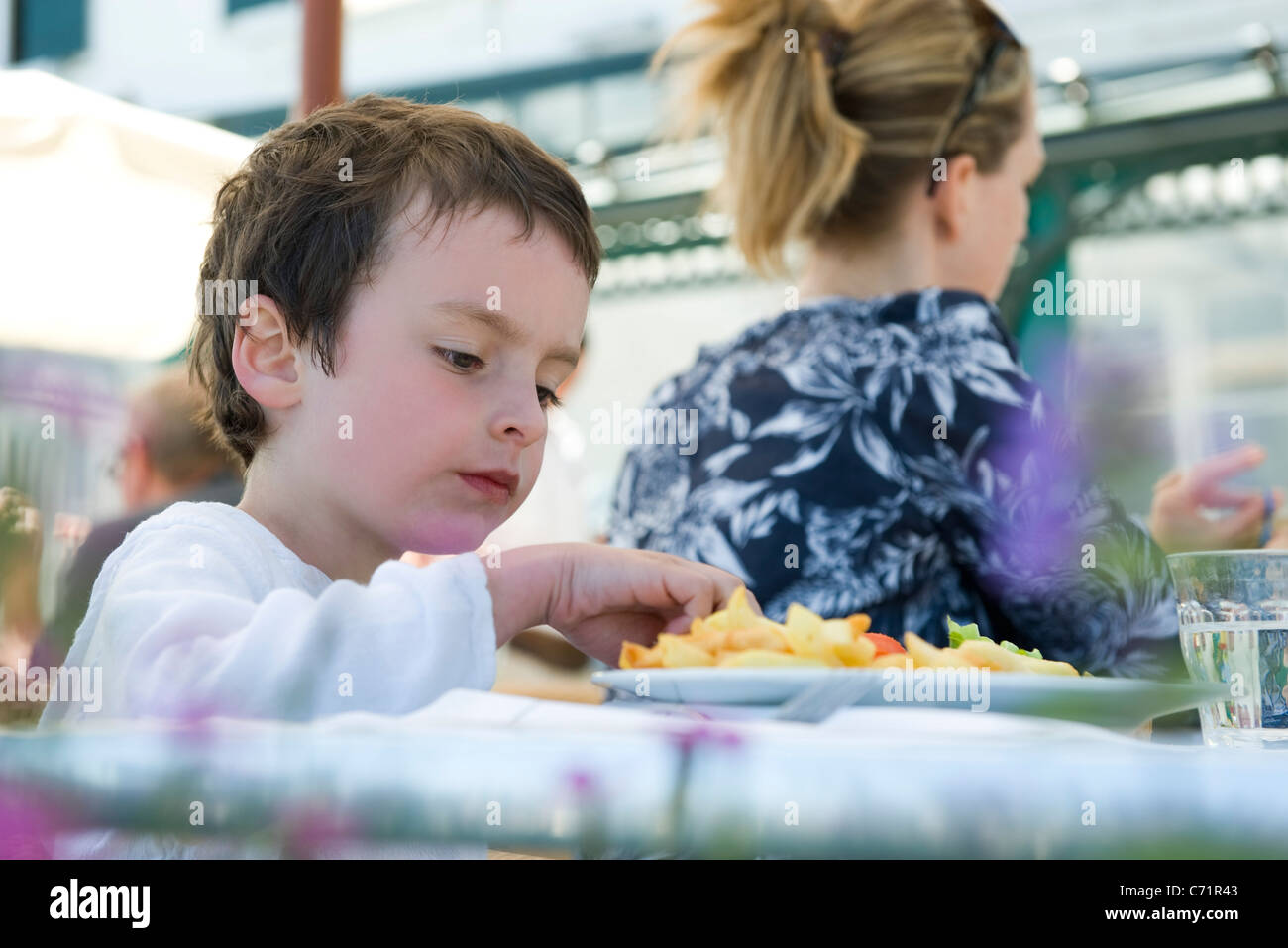 Boy eating in outdoor cafe - Stock Image