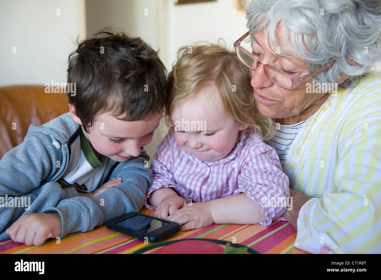 Grandmother and young grandchildren looking at cell phone together - Stock Image