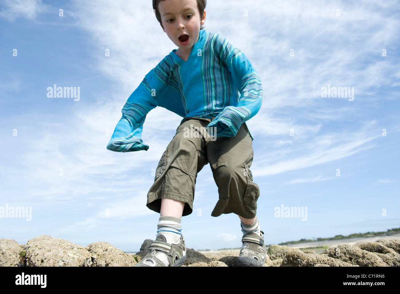 Boy playing outdoors, low angle view - Stock Image