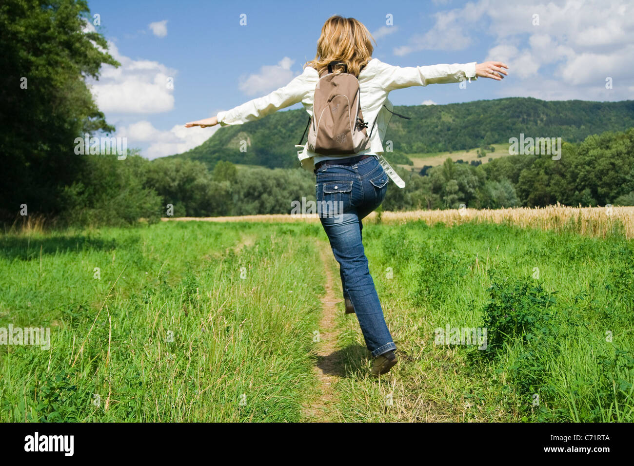 Frolicking woman, jumping for joy - Stock Image